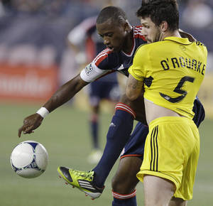Photo -   New England Revolution forward Dimitry Imbongo (92) controls the ball as Columbus Crew defender Danny O'Rourke (5) leans on Imbongo during the first half of an MLS soccer match in Foxborough, Mass., Wednesday, Sept. 5, 2012. (AP Photo/Stephan Savoia)