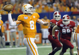 photo -   Tennessee quarterback Tyler Bray (8) passes as North Carolina State defensive end McKay Frandsen (98) defends during the second quarter of the Chick-fil-A Kickoff Game, during an NCAA college football game in Atlanta., on Friday, Aug. 31, 2012. (AP Photo/John Amis)