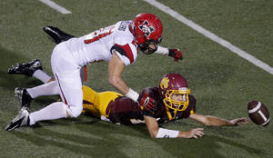 Photo - Mustang's Dakota Sellers, left, and Putnam City North's Chase Sparks go after a Putnam City North fumble during their high school football game at Putnam CIty High School in Oklahoma City, Thursday, Sept. 12, 2013. Putnam City North recovered the ball. Photo by Bryan Terry, The Oklahoman