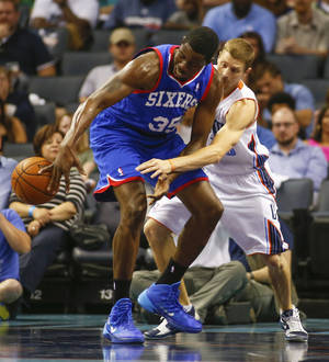 Photo - Philadelphia 76ers center Henry Sims (35) looses control of the ball against Charlotte Bobcats guard Luke Ridnour, right, during the first half of an NBA basketball game in Charlotte, N.C., Saturday, April 12, 2014. (AP Photo/Chris Keane)