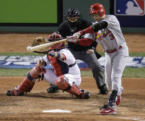 Photo - St. Louis Cardinals' Carlos Beltran hits an RBI single in front of Boston Red Sox catcher Jarrod Saltalamacchia during the seventh inning in Game 2 of baseball's World Series Thursday, Oct. 24, 2013, in Boston. (AP Photo/Charlie Riedel)