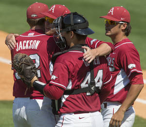 Photo - Arkansas players Zach Jackson, Alex Gosser, Trey Killian and Arkansas' Garrett Rucker celebrate after the team's 4-0 win over Texas A&M during the Southeastern Conference NCAA college baseball tournament Tuesday, May 20, 2014, in Hoover, Ala. (AP Photo/Hal Yeager)