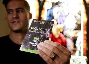 "Photo - Pastor Justice Coleman, founder of Freedom Church poses for a picture with a flyer from his coming service Thursday, April 17, 2014 in Highland Park, Calif. Coleman  is using medical marijuana imagery and catchy word play to attract new worshippers to an Easter sermon series called ""Medicated,"" about seeking fulfillment through God, not drugs. (AP Photo/Chris Carlson)"