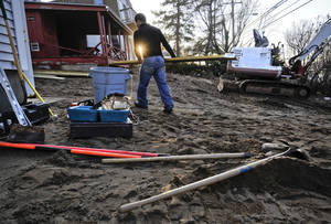 photo - In this Dec. 4, 2012, photo, Reginaldo Ferreira of Russe Builders carries wood to construct a wall to protect a beachfront home in Fairfield, Conn. The national economy is expected to absorb the blow from Sandy with little long-term damage, but in the short term, at least, Sandy is introducing dramatic booms and busts across the Northeast. The effects vary widely across industries, bringing banner years for some while pushing others toward economic ruin. (AP Photo/Jessica Hill)