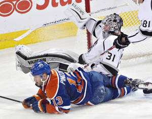 Photo - Los Angeles Kings goalie Martin Jones (31) is crashed into by Edmonton Oilers' Steven Pinizzotto (13) during second-period NHL hockey game action in Edmonton, Alberta, Thursday, April 10, 2014. (AP Photo/The Canadian Press, Jason Franson)