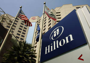 Photo - FILE - In this Tuesday, July 31, 2007, file photo, flags fly outside the Hilton Hotel in Long Beach, Calif., The hotelier, which went private in 2007, priced its initial public offering on Wednesday, Dec. 11, 2013 at $20 per share  in the middle of its expected range, for a total take of $2.35 billion on the sale of 117.6 million shares.  (AP Photo/Reed Saxon, File)