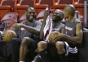 Photo - Miami Heat small forward LeBron James, left, center Joel Anthony, center, and shooting guard Ray Allen, right, laugh as they sit on the bench during team basketball practice on Friday, June 7, 2013, at the American Airlines Arena in Miami. The Heat and the San Antonio Spurs are scheduled to play Game 2 of the NBA Finals, Sunday. (AP Photo/Wilfredo Lee)