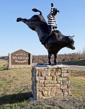 Photo - An Oklahoma State Penitentiary prison rodeo statue is in front of a sign welcoming visitors to McAlester. Photo by Nate Billings, The Oklahoman