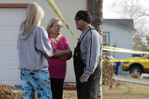 "Photo - Neighborhood residents talk amid crime-scene tape at the scene of an apparent murder-suicide, which officials say left four dead inside a home, according to officials, in Longmont, Colo., Tuesday Dec. 18, 2012.  Weld County sheriff's spokesman Tim Schwartz says dispatchers heard the woman who called 911 scream ""No, no, no,"" and then they heard a gunshot. Schwartz says a man grabbed the phone and said he was going to kill himself, and dispatchers heard another shot.  (AP Photo/Brennan Linsley)"