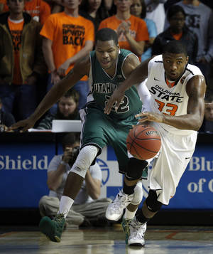Photo - Oklahoma State's Marcus Smart (33) drives up courts as Utah Valley's Chad Ross (22) chases him during the between Oklahoma State University and Utah Valley at Gallagher-Iba Arena in Stillwater, Okla., Tuesday, Nov. 12, 2013. Photo by Sarah Phipps, The Oklahoman