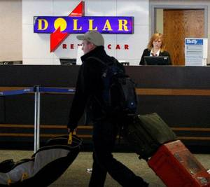 Photo - A Dollar Thrifty employee works behind a counter at Tulsa International Airpor while a traveler passes by. CORY YOUNG/Tulsa World  <strong></strong>