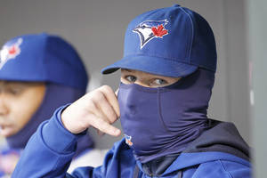 Photo - Toronto Blue Jays third baseman Brett Lawrie imitates talking on a phone as he sits bundled up in the dugout during the first inning of the MLB American League baseball game against the Minnesota Twins where the temperature was 36 degrees at game time in Minneapolis, Tuesday, April 15, 2014.  (AP Photo/Ann Heisenfelt)