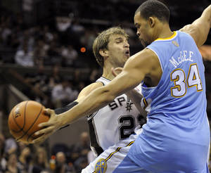Photo -   Denver Nuggets center JaVale McGee, right, blocks a pass-attempt by San Antonio Spurs center Tiago Splitter, of Brazil, during the first half of an NBA preseason basketball game on Friday, Oct. 12, 2012, in San Antonio. (AP Photo/Bahram Mark Sobhani)