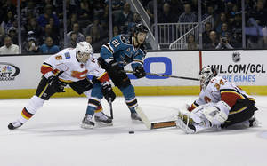 Photo - Calgary Flames goalie Miikka Kiprusoff (34), from Finland, and defenseman Cory Sarich (6) defend a shot by San Jose Sharks left wing T.J. Galiardi (21) during the first period of an NHL hockey game in San Jose, Calif., Friday, April 5, 2013. (AP Photo/Jeff Chiu)