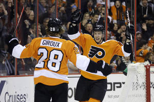 Photo - Philadelphia Flyers' Michael Raffl, right, of Austria, celebrates with Claude Giroux after Raffl scored during the second period of an NHL hockey game against the Montreal Canadiens, Wednesday, Jan. 8, 2014, in Philadelphia. (AP Photo/Matt Slocum)