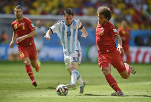 Photo - Argentina's Lionel Messi, center, is challenged by Belgium's Axel Witsel, right, during the World Cup quarterfinal soccer match between Argentina and Belgium at the Estadio Nacional in Brasilia, Brazil, Saturday, July 5, 2014. (AP Photo/Martin Meissner)