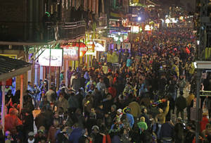 Photo - Mardi Gras crowds in the French Quarter are seen from the balcony of the Royal Sonesta Hotel in New Orleans, Tuesday, March 4, 2014. Rain and unusually cold temperatures caused the crowd to be smaller than previous years.  (AP Photo/Gerald Herbert)