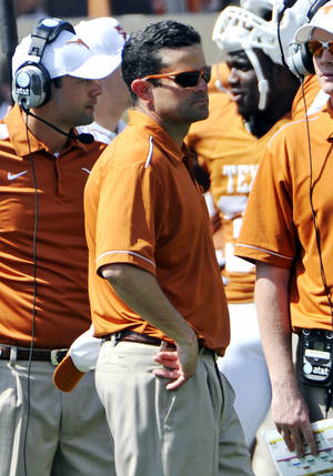 Photo - FILE - In this April 1, 2012 file photo, Texas defensive coordinator Manny Diaz watches during the Orange and White spring NCAA college football game, in Austin, Texas. Texas fired defensive coordinator Manny Diaz on Sunday, Sept. 8, 2013,  less than 24 hours after one of the worst defensive performances in the history of the program. Longhorns coach Mack Brown announced that former Longhorns defensive coordinator and Syracuse coach Greg Robinson will take over the job. (AP Photo/Michael Thomas, File)