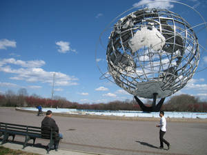 Photo - In this April 9, 2014, photo, a man walks near the Unisphere, a 12-story steel globe that debuted 50 years ago at the 1964 World's Fair in the Queens borough of New York. It's located in Flushing Meadows Park outside the Queens Museum of Art, and it's one of a number of World's Fair sites that is still in place. (AP Photo/Beth J. Harpaz)