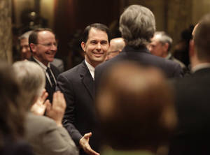 Photo - Wisconsin Governor Scott Walker greets legislators while making his way into the Assembly chamber for his state budget address at the Wisconsin State Capitol in Madison, Wis. Wednesday, February 20, 2013. (AP Photo/Wisconsin State Journal, John Hart)