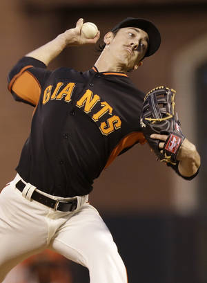 Photo - San Francisco Giants pitcher Tim Lincecum throws against the Oakland Athletics during the second inning of a spring exhibition baseball game in San Francisco, Friday, March 28, 2014. (AP Photo/Jeff Chiu)