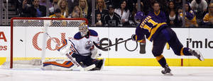 Photo - Los Angeles Kings center Anze Kopitar (11), of Yugoslavia scores on Edmonton Oilers goalie Richard Bachman, left, during the shootout of an NHL hockey game Sunday, Oct. 27, 2013, in Los Angeles. Kings won 2-1 in a shootout. (AP Photo/Alex Gallardo)