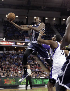 Photo - Oklahoma City Thunder forward Kevin Durant, left, drives to the basket against Sacramento Kings' Jason Thompson during the first quarter of an NBA basketball game in Sacramento, Calif., Tuesday, Dec. 3, 2013. (AP Photo/Rich Pedroncelli)