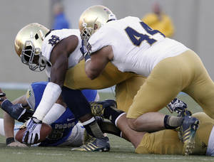 Photo - Notre Dame linebacker Jaylon Smith, front left, picks up a ball fumbled by Air Force quarterback Nate Romine, back left, as Notre Dame linebacker Carlo Calabrese, front right, covers in the third quarter of Notre Dame's 45-20 victory in an NCAA football game in Air Force Academy, Colo., Saturday, Oct. 26, 2013. (AP Photo/David Zalubowski)