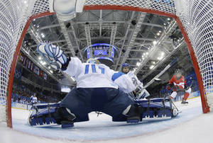 Photo - Rebecca Johnston's of Canada shot sails past Goalkeeper Noora Raty of Finland for a goal during the third period of the 2014 Winter Olympics women's ice hockey game at Shayba Arena, Monday, Feb. 10, 2014, in Sochi, Russia. Canada defeated Finland 3-0. (AP Photo/Matt Slocum, Pool)