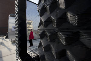 Photo - A visitor passes a 3D printer, rear, as she looks at part of a printed canal house, foreground, in Amsterdam, Netherlands, Thursday, March 13, 2014. Dutch architecture firm Dus has embarked on a project to build a 21st-century version of a classic Amsterdam canal house, printing it out piece by piece with an oversized 3-D printer, and then slotting them together like oversized Lego blocks. The goal is to discover and share the potential uses of 3-D printing in construction by creating new materials, trying out designs and testing building techniques. (AP Photo/Peter Dejong)