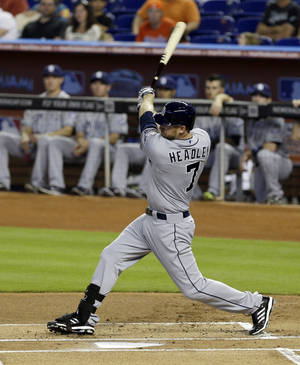 Photo - San Diego Padres' Chase Headley follows through on a base hit against the Miami Marlins in the first inning of a baseball game in Miami, Sunday, April 6, 2014. (AP Photo/Alan Diaz)