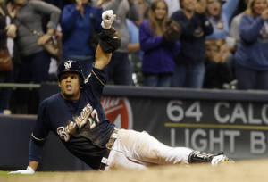 Photo - Milwaukee Brewers' Carlos Gomez reacts after hitting a triple during the sixth inning of a baseball game against the St. Louis Cardinals, Sunday, Sept. 22, 2013, in Milwaukee. (AP Photo/Morry Gash)