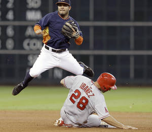 Photo - Houston Astros second baseman Jose Altuve, top, jumps over Los Angeles Angels' Raul Ibanez (28) to watch his throw be too late to complete the double play on Angels' Howie Kendrick in the seventh inning of a baseball game on Sunday, April 6, 2014, in Houston. (AP Photo/Pat Sullivan)