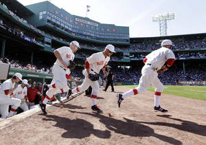 Photo -   Boston Red Sox players take the field for a baseball game against the New York Yankees in throw-back uniforms of 1912 at Fenway Park in Boston, Friday, April 20, 2012. The Red Sox are celebrating the100th anniversary of the first regular-season game at Fenway Park. (AP Photo/Elise Amendola)