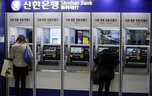 Photo - Customers use the automated teller machine at a branch of Shinhan Bank in Seoul, South Korea, Thursday, March 21, 2013. Investigators have traced a coordinated cyberattack that paralyzed tens of thousands of computers at six South Korean banks and media companies to a Chinese Internet Protocol address, authorities in Seoul said Thursday. (AP Photo/Lee Jin-man)