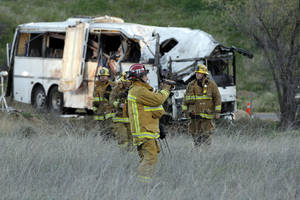 Photo - Investigators examine the scene of a tour bus accident Monday Feb. 4, 2013 in the mountains of Southern California near San Bernardino.  The accident killed at least 8 people. ( AP Photo/Nick Ut)