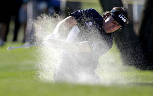 photo - Phil Mickelson hits from a fairway bunker on the fifth hole during the first round of the Humana Challenge golf tournament at the La Quinta Country Club in La Quinta, Calif.,  Thursday, Jan. 17, 2013. (AP Photo/Chris Carlson)