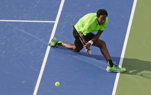 Photo - Gael Monfils, of France, returns a shot against Grigor Dimitrov, of Bulgaria, during the fourth round of the 2014 U.S. Open tennis tournament, Tuesday, Sept. 2, 2014, in New York. (AP Photo/Mike Groll)