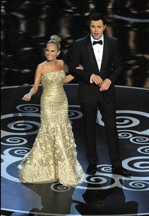 "Photo - Host Seth MacFarlane, right, and actress Kristin Chenoweth perform a song dedicated to the ""losers"" during the finale of the Oscars at the Dolby Theatre on Sunday Feb. 24, 2013, in Los Angeles.  (Photo by Chris Pizzello/Invision/AP)"