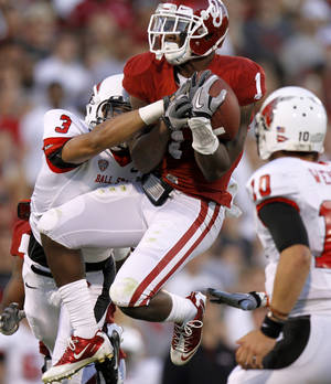 Photo - Oklahoma's Tony Jefferson (1) intercepts a pass beside Ball State's Willie Snead during the college football game between the University of Oklahoma Sooners (OU) and the Ball State Cardinals at Gaylord Family-Memorial Stadium on Saturday, Oct. 01, 2011, in Norman, Okla. Photo by Bryan Terry, The Oklahoman