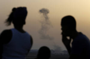"""Photo - Israelis stand on a hill at the Israeli town of Sderot, overlooking the Gaza Strip, as they watch smoke rising following an Israeli strike on Gaza, Saturday, July 12, 2014.  Ignoring international appeals for a cease-fire, Israel on Saturday widened its range of Gaza bombing targets to civilian institutions with suspected Hamas ties and announced it would hit northern Gaza """"with great force"""" to prevent rocket attacks from there on Israel. More than 150 Palestinians have been killed in five days of bombardment.  (AP Photo/Lefteris Pitarakis)"""
