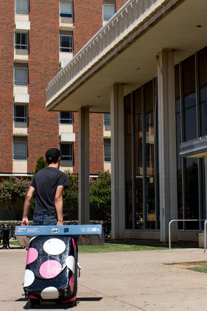 photo - Jordan Gilmez rolls a suitcase toward a residence hall Monday. Students moved into the Oklahoma State University dorms Monday, Aug. 13, 2012, in Stillwater, Okla. Photos by Mitchell Alcala for the Oklahoman <strong>Mitchell Alcala - Mitchell Alcala for the Oklahoma</strong>