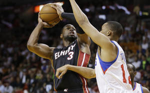 photo - Philadelphia 76ers' Evan Turner (12) tries to block Miami Heat's Dwyane Wade (3)  during the first half of a NBA basketball game in Miami, Friday, March 8, 2013. (AP Photo/J Pat Carter)