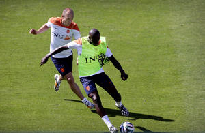 Photo - Arjen Robben, left, and Bruno Martins Indi, right, from the Netherlands soccer team run after the ball during a training session in Rio de Janeiro, Brazil, Sunday June 8, 2014.  The Netherlands play in group B of the 2014 soccer World Cup. (AP Photo/Wong Maye-E)