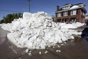 Photo - A pile of snow towers over the sidewalk on 9th and St. Joseph Streets in downtown Rapid City, S.D., Monday, Oct. 7, 2013.. (AP Photo/Rapid City Journal, Benjamin Brayfield)