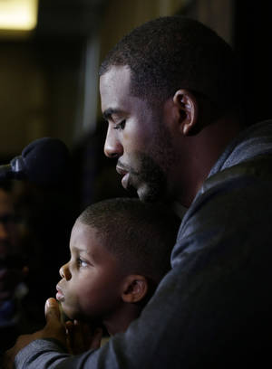 Photo - Los Angeles Clippers' Chris Paul holds his son Chris Paul Jr., 4, during the NBA All Star basketball news conference, Friday, Feb. 14, 2014, in New Orleans. The 63rd annual NBA All Star game will be played Sunday in New Orleans.(AP Photo/Gerald Herbert)