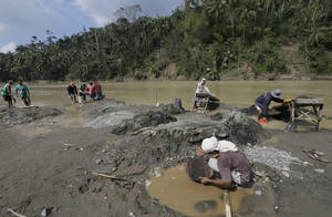 Photo - In this photo taken on Sunday Dec. 9, 2012, small-scale miners pan for gold by the riverside of Guijo River at Mawab township, Compostela Valley in southern Philippines. The miners rushed to the river three days after Typhoon Bopha slammed Compostela Valley, a mining province. The number of people missing after a typhoon devastated the Philippines jumped to nearly 900 as nearly 400,000 people, mostly from Compostela Valley and nearby Davao Oriental province, have lost their homes. (AP Photo/Bullit Marquez)
