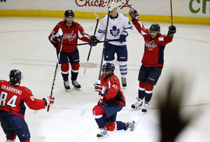Photo - Washington Capitals right wing Joel Ward (42) celebrates his goal with center Mikhail Grabovski (84), center Marcus Johansson (90) and defenseman Mike Green (52), with Toronto Maple Leafs center Tyler Bozak (42) nearby, during the third period of an NHL hockey game, Friday, Jan. 10, 2014, in Washington. The Capitals won 3-2. (AP Photo/Alex Brandon)