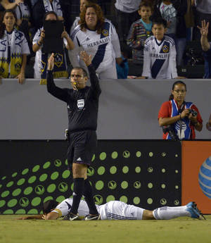 photo -   An official, top, calls for trainers as Los Angeles Galaxy's Landon Donovan lies on the ground after injuring his leg during the second half of an MLS soccer match against Real Salt Lake, Saturday, Oct. 6, 2012, in Carson, Calif. Real Salt Lake won 2-1. (AP Photo/Mark J. Terrill)