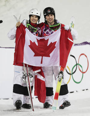 Photo - Canada's Alex Bilodeau, right,  celebrates with compatriot Mikael Kingsbury after after Bilodeau won gold and Kingsbury took silver in the men's moguls final at the Rosa Khutor Extreme Park at the 2014 Winter Olympics, Monday, Feb. 10, 2014, in Krasnaya Polyana, Russia.  (AP Photo/Andy Wong)